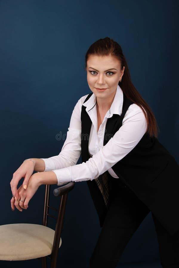 Le den blåa dräkten för affärskvinnan klädde anseende mot blå bakgrund med korsade armar royaltyfri foto