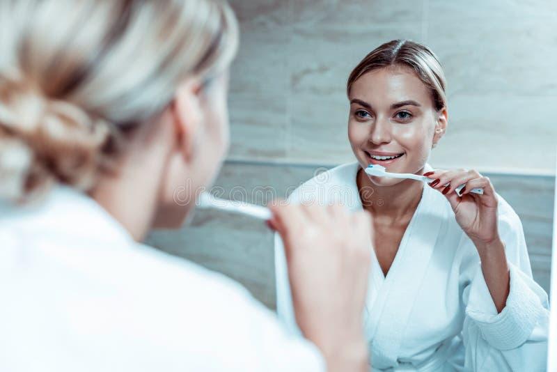 Le den blonda damen som gör ren hennes tänder med tandkräm royaltyfria foton