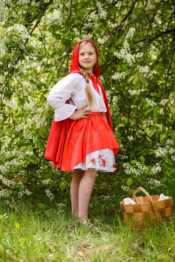 Le den blonda flickan som poserar i en klänning av near gröna träd för liten röd ridninghuv royaltyfri fotografi