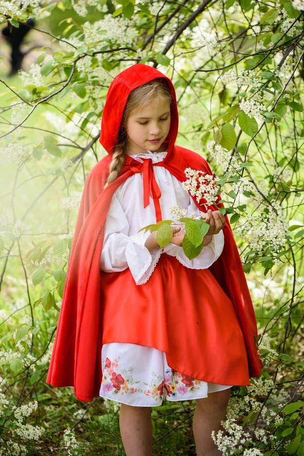 Le den blonda flickan som poserar i en klänning av near gröna träd för liten röd ridninghuv arkivfoton