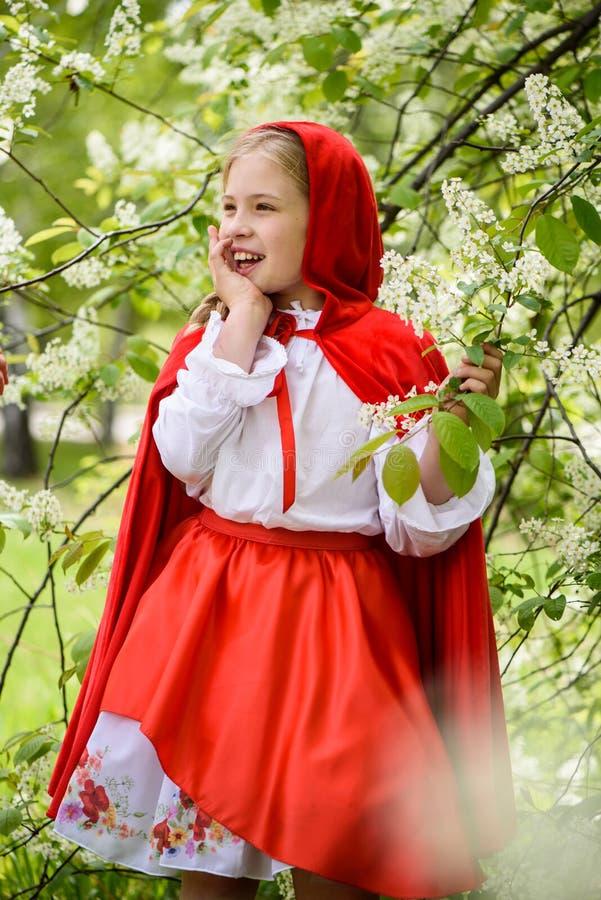 Le den blonda flickan som poserar i en klänning av near gröna träd för liten röd ridninghuv royaltyfri foto