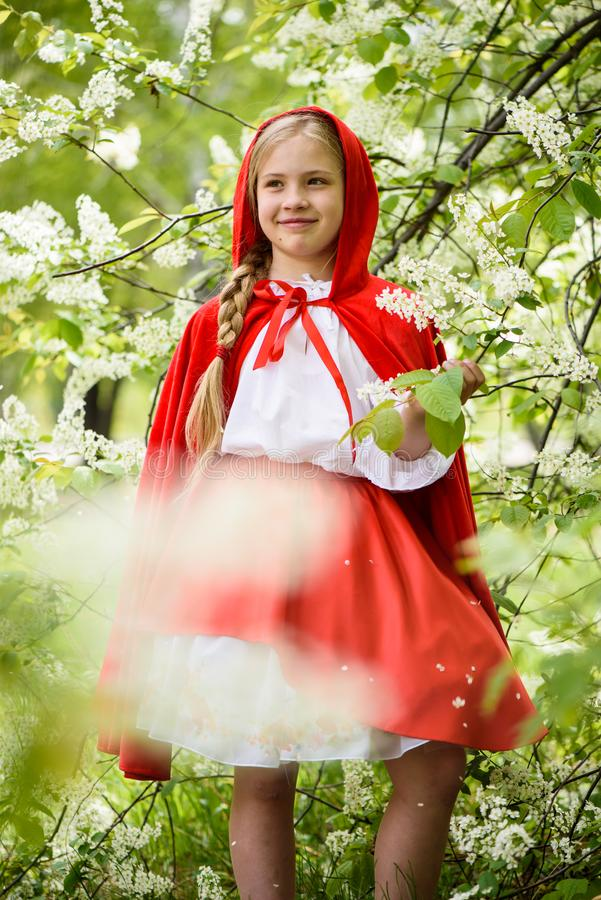 Le den blonda flickan som poserar i en klänning av near gröna träd för liten röd ridninghuv arkivbilder