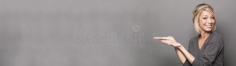 Le den blonda kvinnan som visar ett tomt utrymme för vänstersidahandsida royaltyfri fotografi