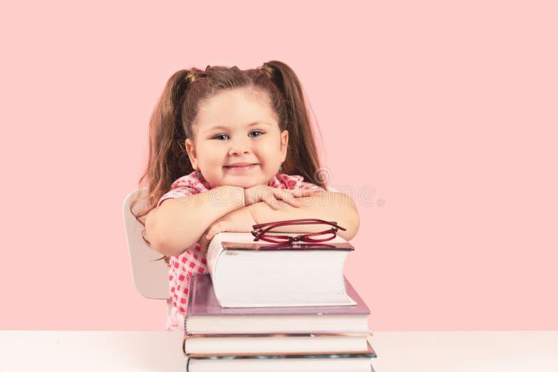 le den blonda lilla gulliga flickan som studerar på böcker royaltyfri foto