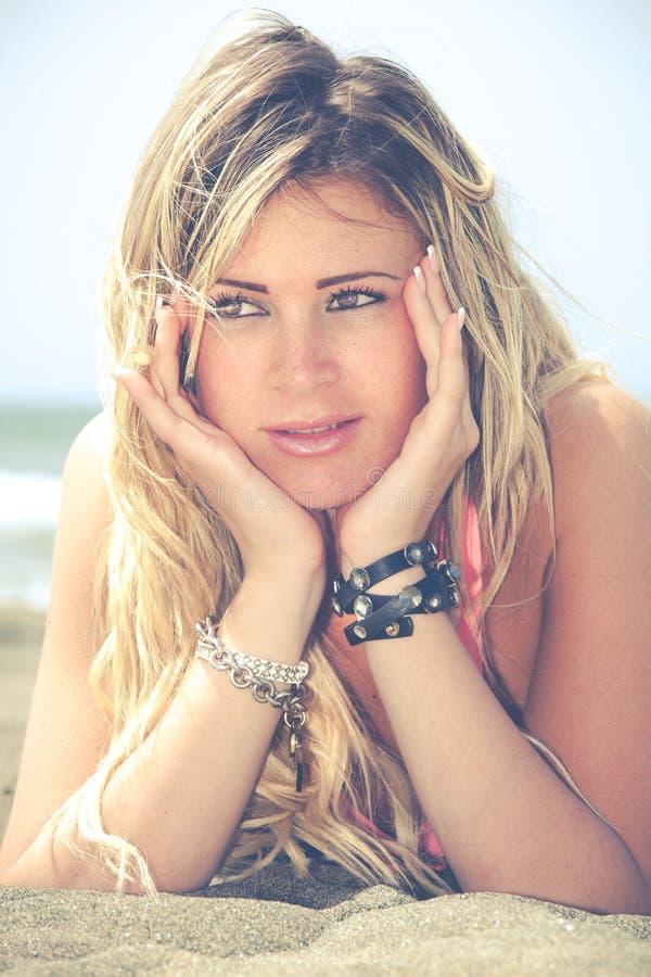 Le den blonda lyckliga flickan på havet som ligger på stranden Två händer under henne framsida arkivbilder