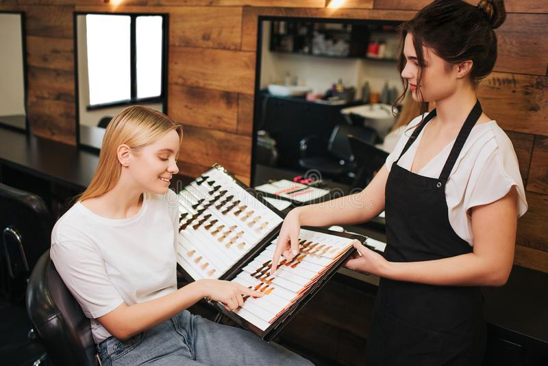 Le den blonda unga kvinnan och frisören som väljer hårfärg från paletten, innan att färga i skönhetsalong _ royaltyfri foto