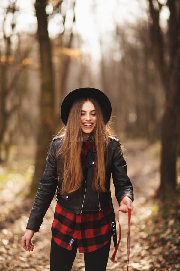 Le den brunhåriga kvinnan med hatten i skog royaltyfri bild