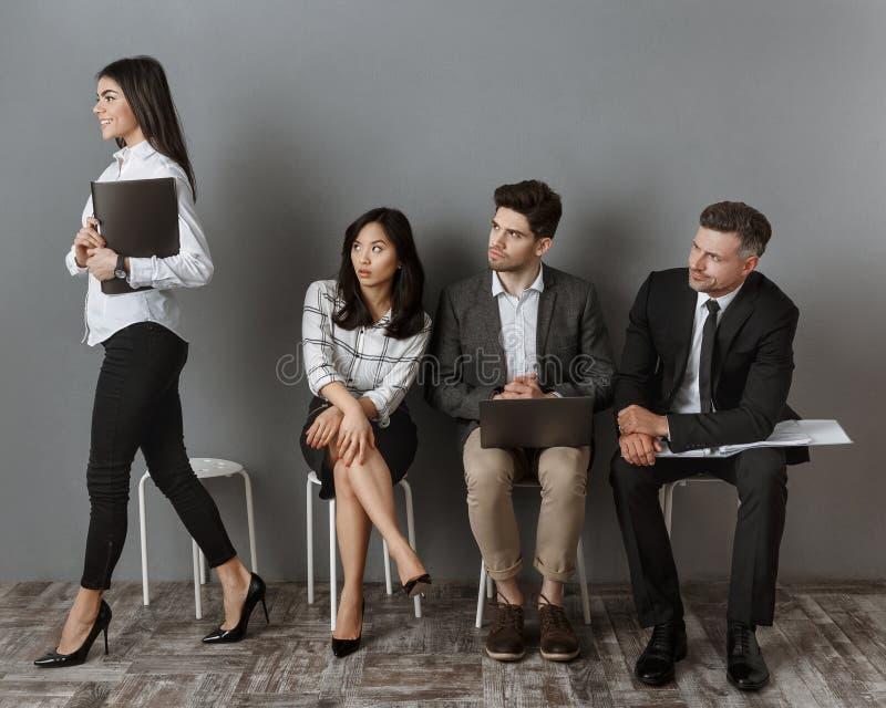 le den caucasian affärskvinnan som går för jobbintervju medan multietniska kollegor som ser henne arkivfoton