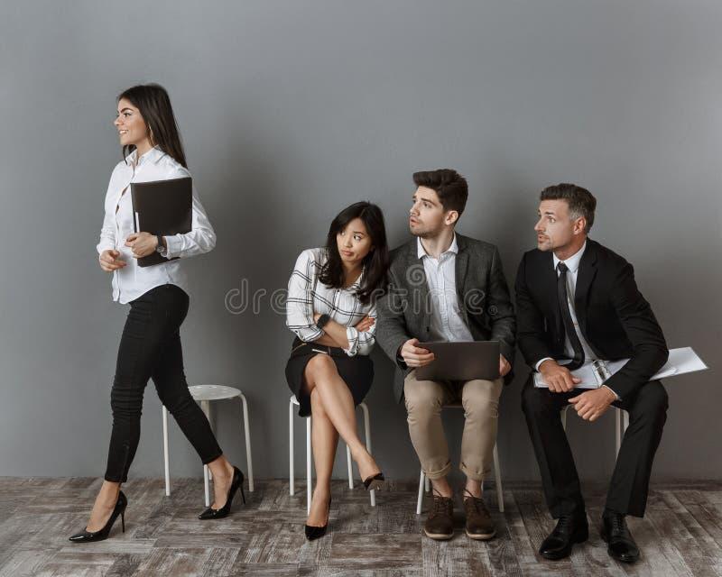 le den caucasian affärskvinnan som går för jobbintervju medan multietniska kollegor som ser henne arkivbilder