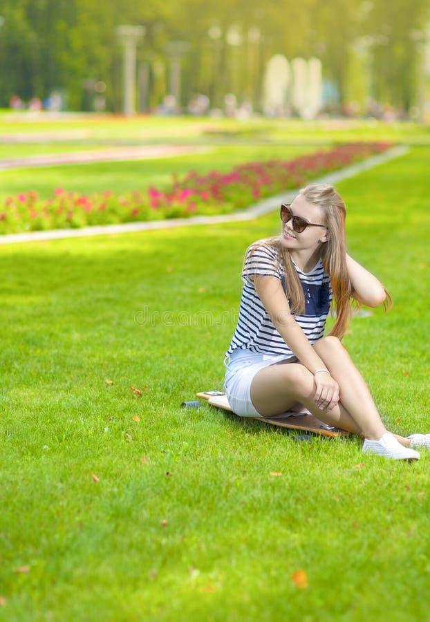 Le den Caucasian blonda tonårs- flickan med Longboard i grön sommar parkera royaltyfri bild