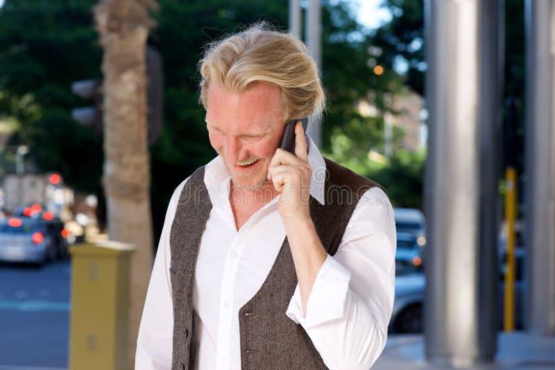 Le den caucasian mannen på stadsgatan som talar på mobiltelefonen royaltyfria bilder