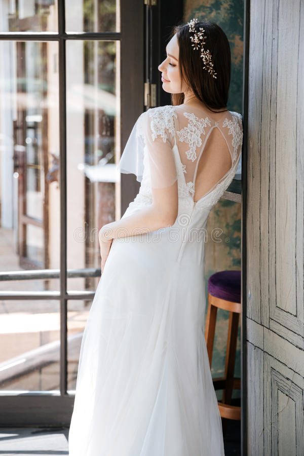 Le den charmiga bruden i den vita klänningen och kransen royaltyfri bild