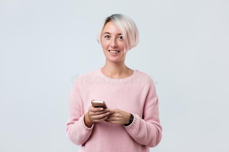 Le den charmiga caucasian kvinnan med den korta färgade hårinnehavmobiltelefonen royaltyfria bilder