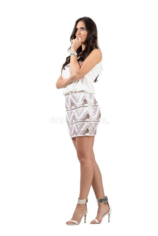 Le den eftertänksamma eleganta kvinnan med handen på hennes haka som bort ser royaltyfri bild
