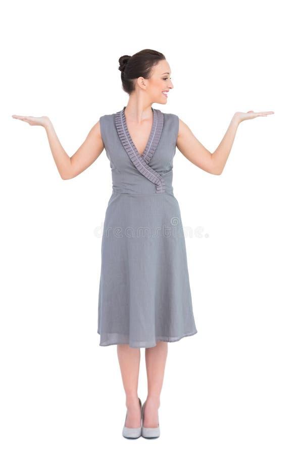 Le den eleganta kvinnan i den flotta klänningen som poserar upp händer royaltyfri foto