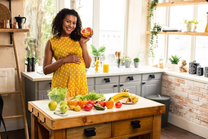 Le den förväntansfulla modern som rymmer en halva av grapefrukten fotografering för bildbyråer