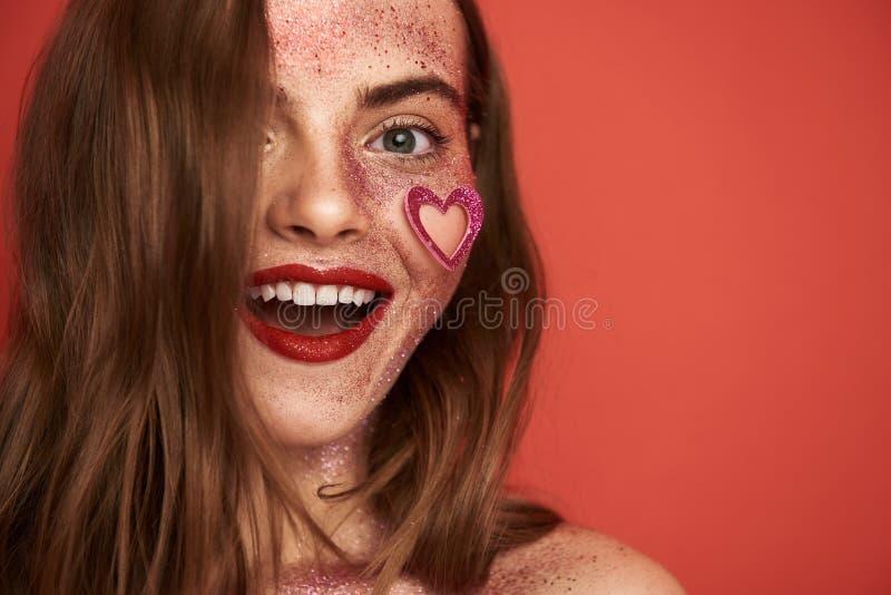Le den f?rv?nade modellen med id?rik makeup som poserar f?r kamera i studio royaltyfri fotografi