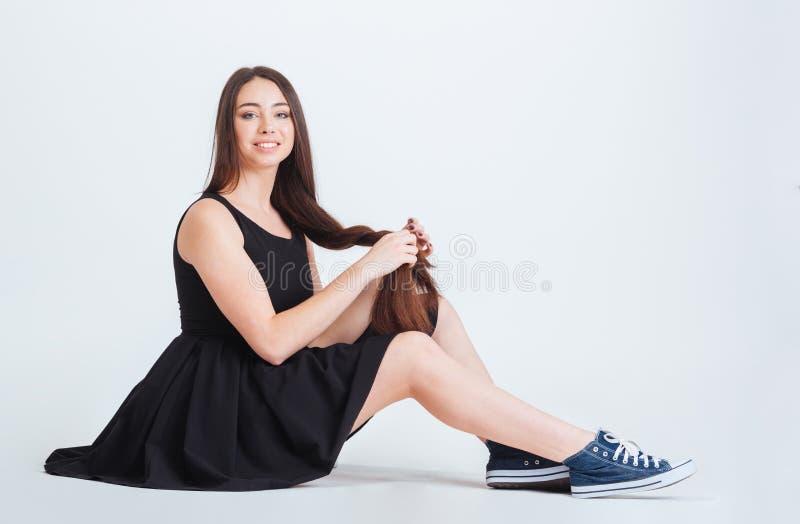 Le den flätad tråden för för kvinnasammanträde och danande med hennes långa hår royaltyfri fotografi