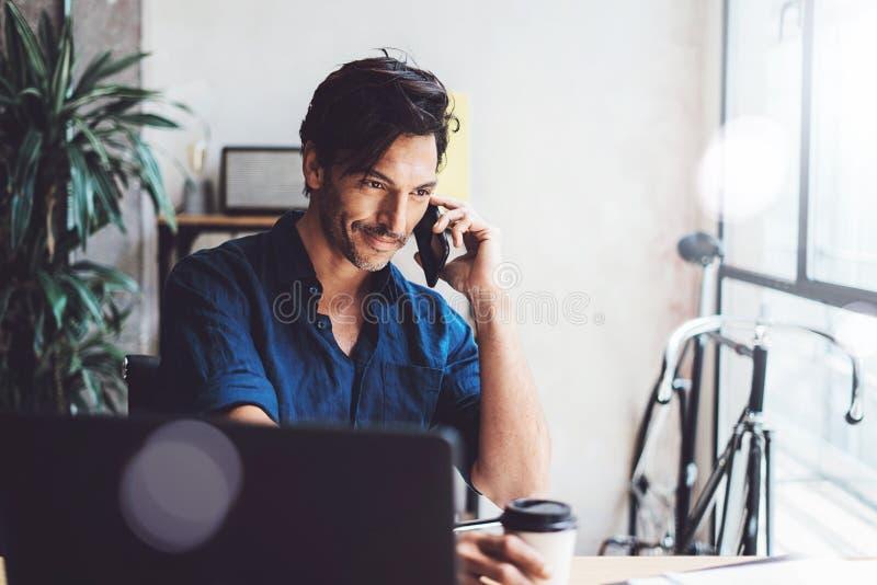Le den funktionsdugliga moderna mobila datoren för latinamerikansk affärsman, medan sitta på trätabellen på det soliga kontoret m arkivbild