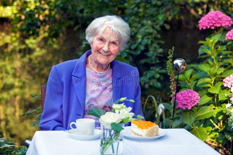 Le den gamla kvinnan med mellanmål på den trädgårds- tabellen arkivbilder