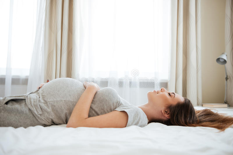Le den gravida unga kvinnan som ligger och kopplar av på säng arkivfoton