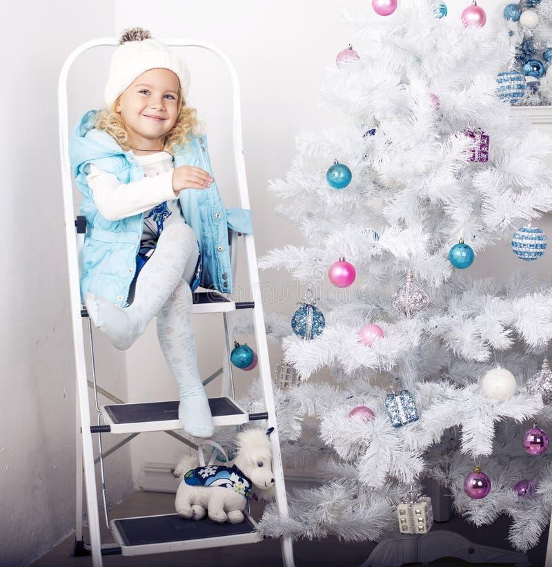 Le den gulliga flickan som poserar bredvid en dekorerad julgran royaltyfri foto