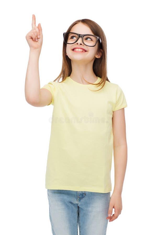 Le den gulliga lilla flickan i svart glasögon royaltyfria foton