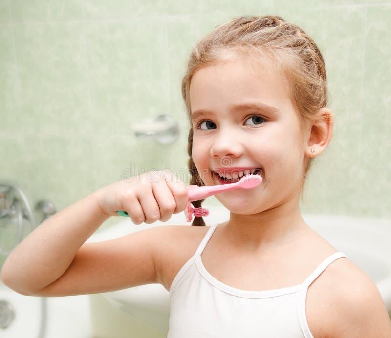 Le den gulliga lilla flickan som borstar tänder royaltyfria bilder