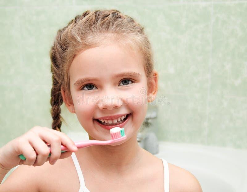 Le den gulliga lilla flickan som borstar tänder i badrum arkivfoto