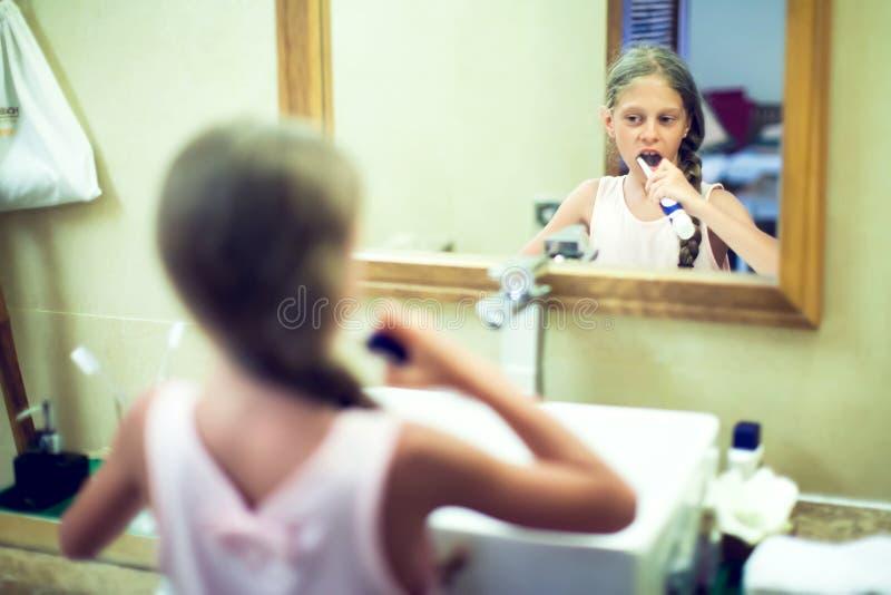 Le den gulliga lilla flickan som borstar tänder i badrum Hygien lurar royaltyfria bilder