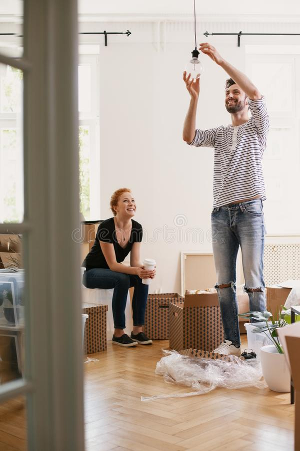 Le den hängande lampan för man, medan möblera det nya hemmet efter inflyttning med hans lyckliga fru royaltyfria bilder