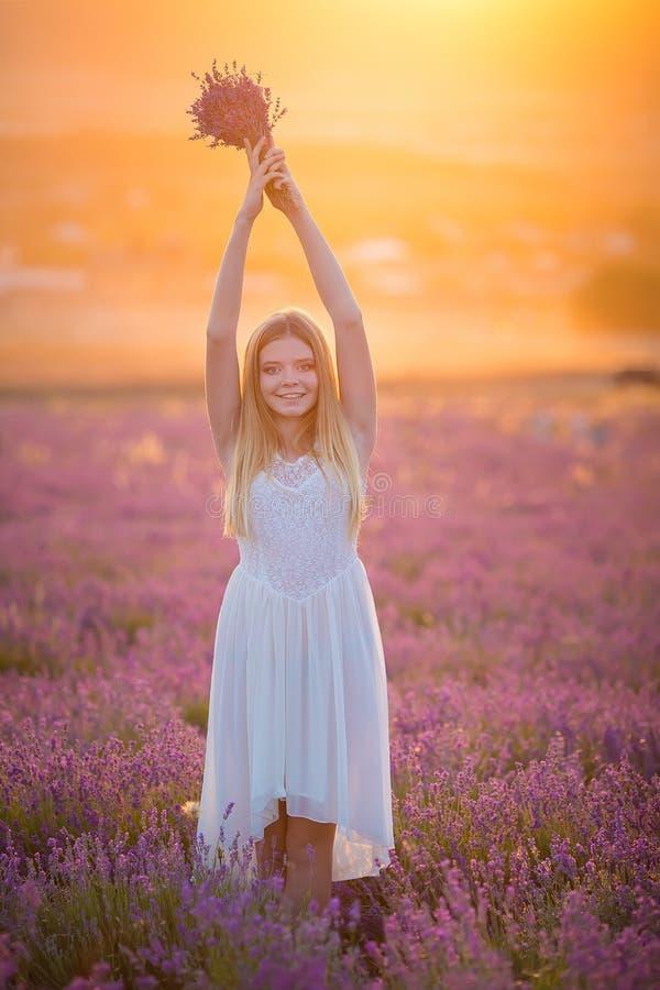 Le den härliga blonda dammodellen på lavendelfält tyck om sommardagen som bär den luftiga whitklänningen med buketten av blommor fotografering för bildbyråer