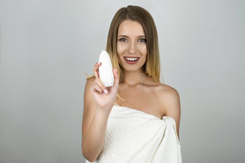 Le den härliga blonda kvinnan i den vita handdukinnehavantiperspiranten i hennes hand isolerade vita bakgrund royaltyfria bilder