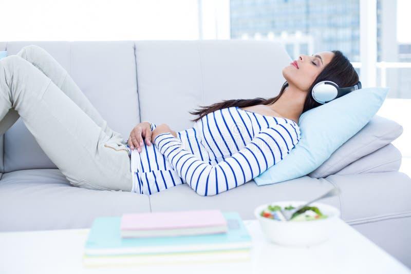 Le den härliga brunetten som kopplar av på soffan och den lyssnande musiken royaltyfri foto