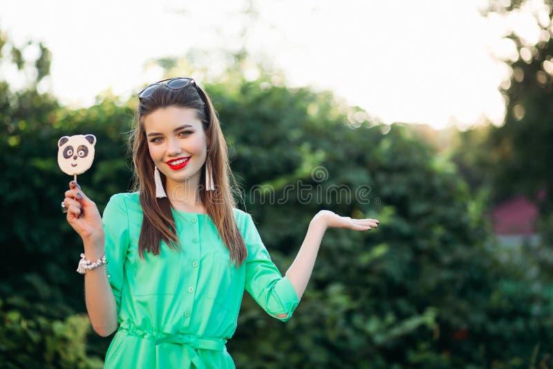 Le den härliga flickan i grön visning på sidan och den hållande godisen gilla pandan arkivfoton