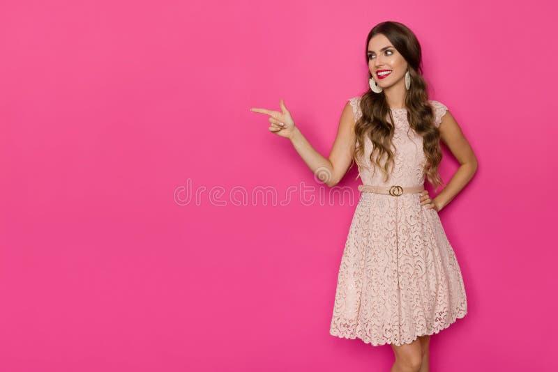 Le den härliga kvinnan i beiga snöra åt Mini Dress Is Looking Away och att peka fotografering för bildbyråer
