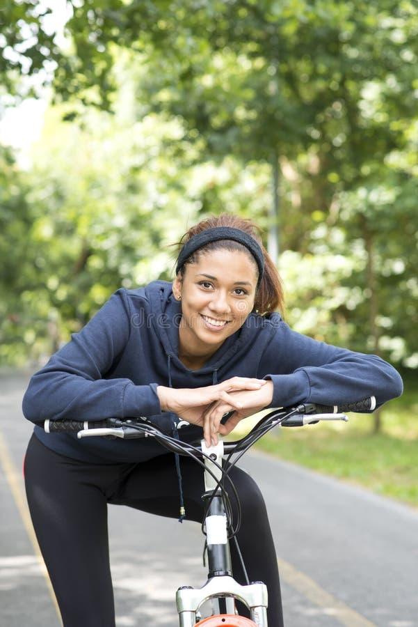 Le den härliga kvinnan som övar med cykeln som är utomhus- royaltyfri bild