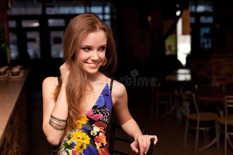 Le den härliga unga flickan bak räknaren på stången royaltyfri fotografi