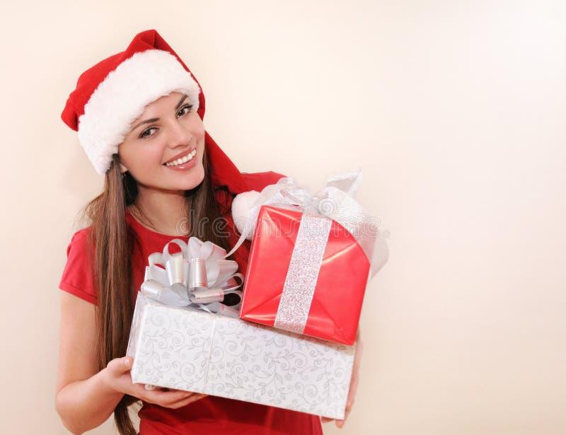 Le den härliga unga kvinnan i jultomtenhatt med gåvor för jul arkivfoto