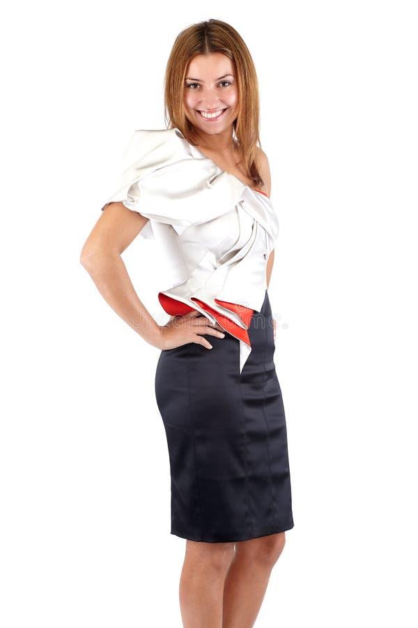 Le den härliga unga kvinnan i den svarta vita röda klänningen som från sidan står och se kameran Studioskott som kantjusteras ned fotografering för bildbyråer