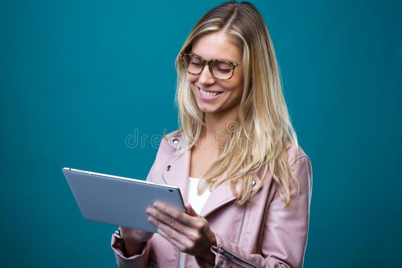 Le den härliga unga kvinnan med glasögon som arbetar med den digitala minnestavlan över blå bakgrund arkivbilder