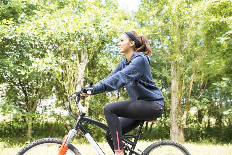 Le den härliga unga kvinnan som övar med cykeln som är utomhus- arkivbilder