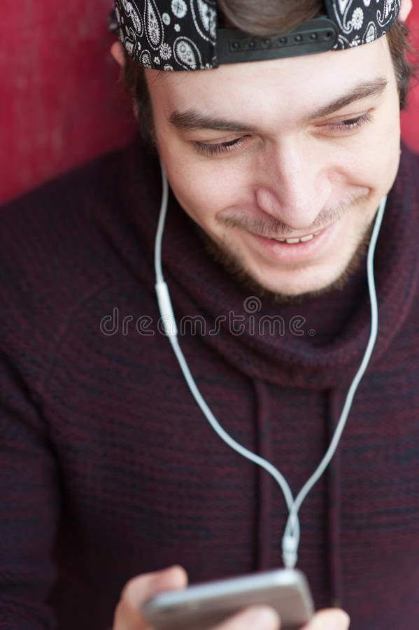 Le den härliga unga mannen med ett skägg med en smartphone och bära hörlurar arkivbild