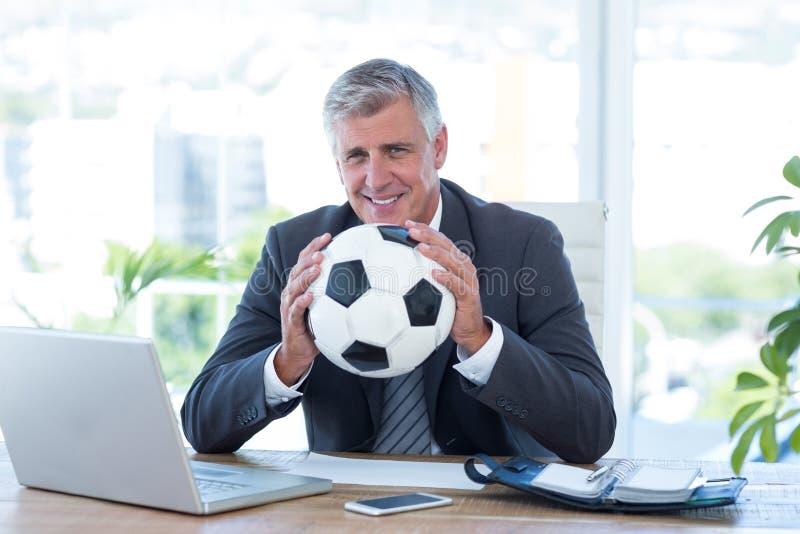 Le den hållande fotbollbollen för affärsman fotografering för bildbyråer