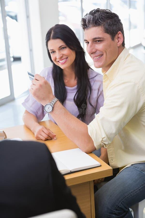 Le den hållande kreditkorten för par för att köpa en bil royaltyfri fotografi