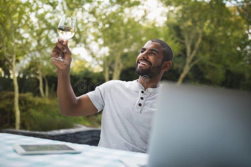 Le den hållande vinglaset för man, medan sitta på farstubron arkivfoto