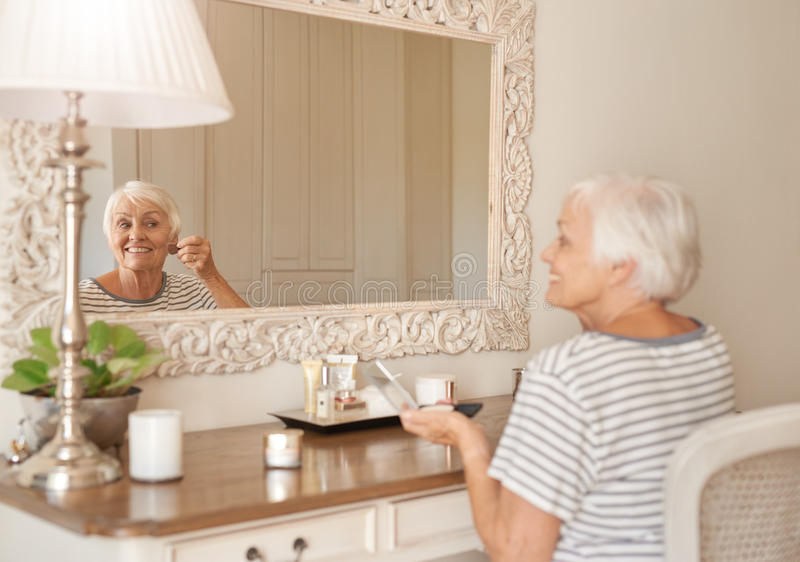 Le den höga kvinnan som hemma applicerar makeup i en spegel fotografering för bildbyråer