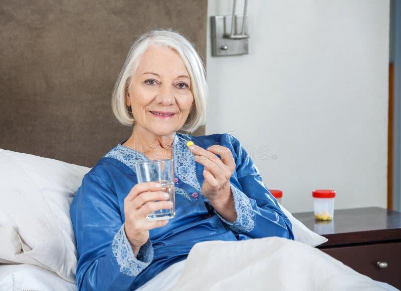 Le den höga kvinnan som tar medicin på sjukvård arkivbilder