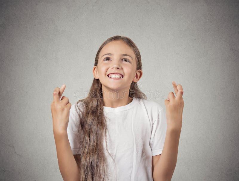 Le den hoppfulla flickan som korsar henne hoppas för fingrar royaltyfria bilder