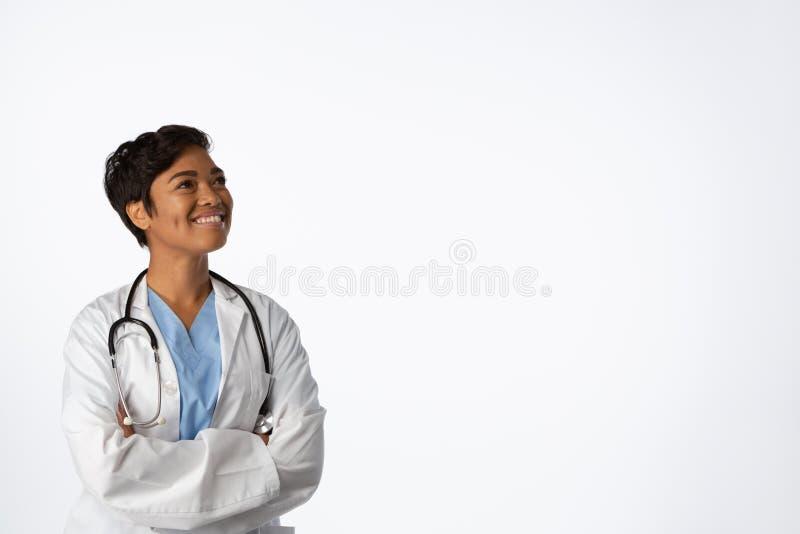 Le den hoppfulla kvinnliga doktorn med korsade armar arkivfoton